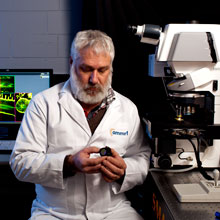 NEAT_PCE bearded technician in white coat examining equipment
